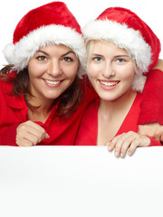 Two girls with santa hat smiling and showing copyspace