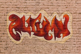 The word Autumn in street graffiti style placed upon brick wall
