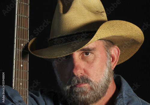 A Cowboy with a Gray Beard and a Guitar