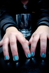 Fingers with nails painted teal