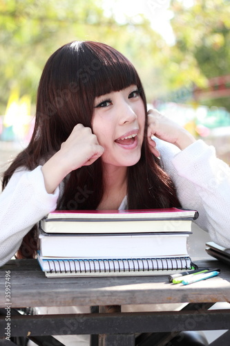 A smiling Asian student is studying.