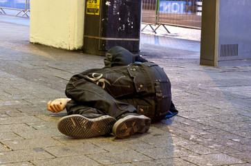 Homeless man sleeps on pavement