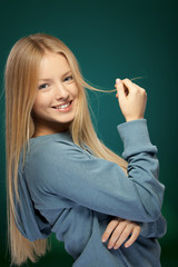 Portrait of young beautiful blond female over green