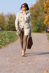Full length, walking woman in autumn park