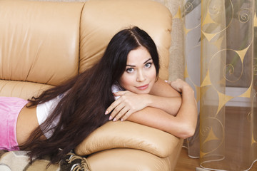 beautiful young woman lying on the couch at home