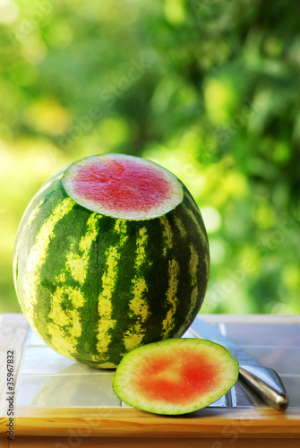 Watermelon and knife on table.