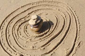Stones pyramid at the beach, circles in the sand