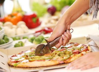 Slicing fresh pizza