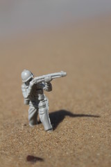 Toy soldier shooting, standing in the sea water