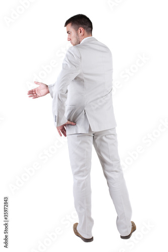 businessman extending hand to shake. Rear view.