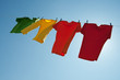 Colorful clothes hanging to dry in the blue sky