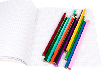 Exercise book with colored pencils isolated over white