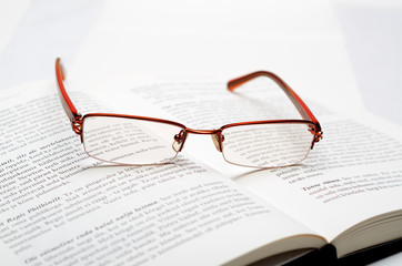 Reading glasses lying on the open book