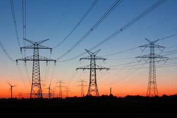 Strommasten bei Sonnenuntergang, am Horizont Windräder