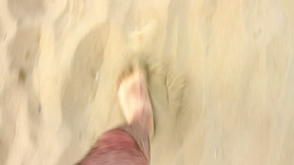 A man's feet as he walks in to the sea