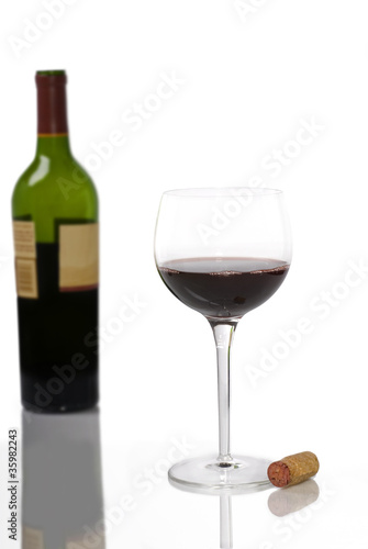 A Glass of Red Wine on White with Bottle in Background