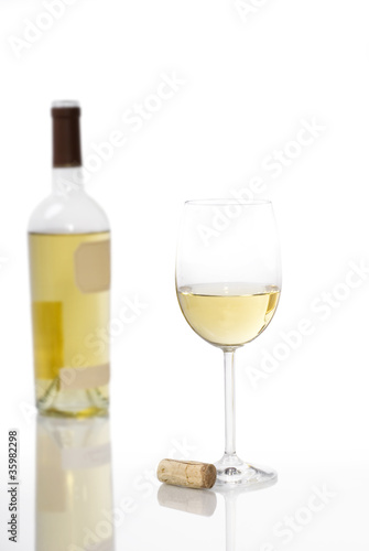 Glass of White Wine with Bottle in Background
