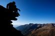 Silhouette of man sitting on rock above mountain range
