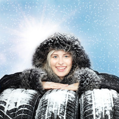 Smiling woman with warm coat and winter tires in the snow