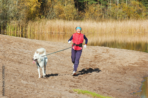 The sports woman with a dog run along coast of the rivers