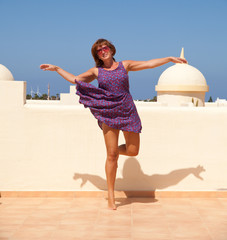 age doesn't matter - tanned, fit middle-aged woman dances on the