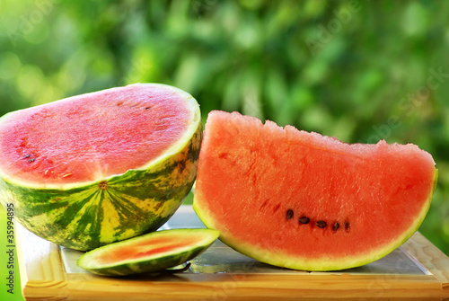 Watermelon and slice on table.