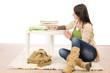 Student teenager girl write homework sitting floor