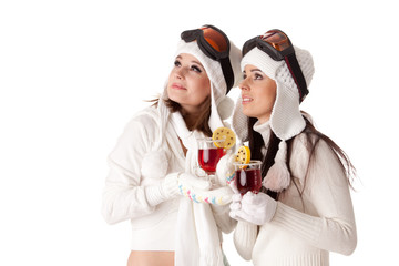 Young women in winter clothes and ski glasses drink mulled wine.
