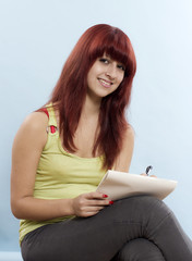 Portrait of young attractive girl sitting with notebook