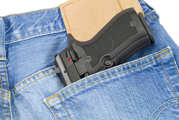 Hand fire arm weapon in blue jeans back pocket