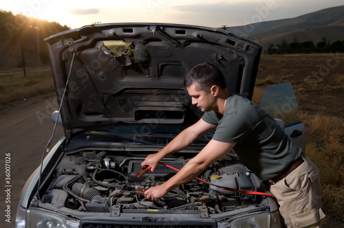 Adult man using jumper cables to start a car battery.