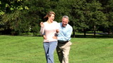 Happy elderly senior couple running  in park