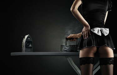 Vintage sexy maid with iron audio speakers on black background