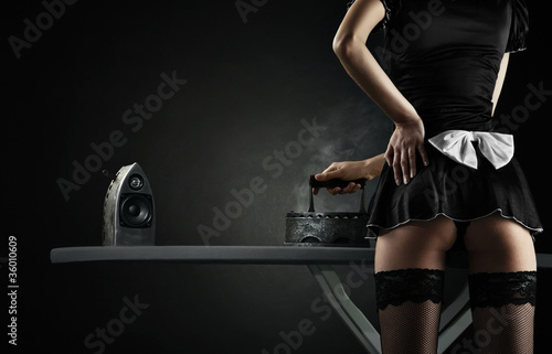 Vintage sexy maid with iron audio speakers on black background - 36010609