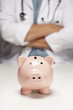 Doctor with Folded Arms Behind Piggy Bank