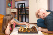 Father and daughter play chess on the floor.