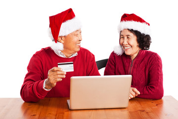 Senior Asian couple shopping online celebrating Christmas