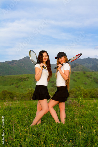 Two women tennis players in  T-shirt with rackets