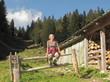 Frau bei Wanderung sitzt auf Zaun