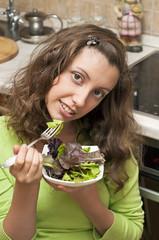 Девушка ест салат из свежей зелени