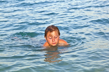 boy enjoys the beautiful water of the ocean