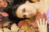 real young woman lying on fallen leaves