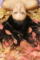 Beautiful smiling girl laying down on red-brown leaves
