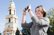Young beautiful woman photographing city's attractions, outdoors