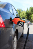 Refueling nozzle in the tank black car at fuel filling column