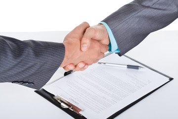 businessmen handshake after sign contract, desk with document