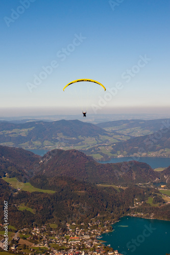 paragliding over lake and mountains in austrian Alps