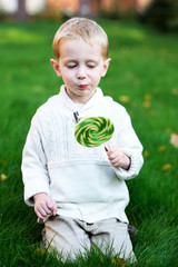 Little boy with big lollipop on a green lawn