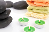 Therapeutic stones with towels and candles poster