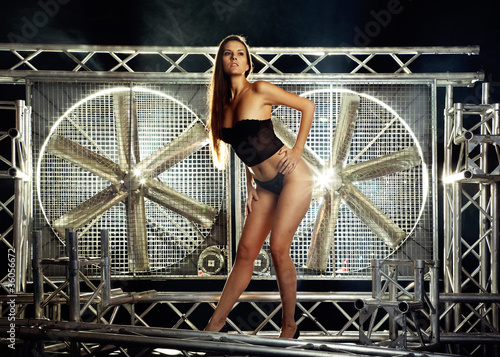 sexy top model in lingerie on a stage with huge turbo fan behind